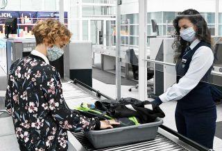 Reisende und Sicherheitsfachkraft mit Mundschutz am Münchner Flughafen