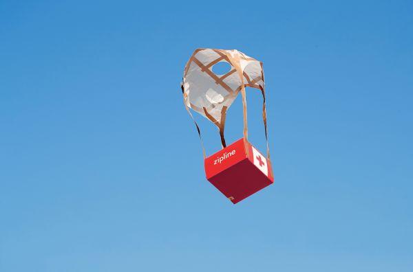 Die Ladung der Zipline-Drohne schwebt an einem Papier-Fallschirm zu Boden